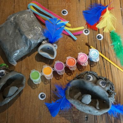 bag of clay, googly eyes, pipe-cleaners, feathers, paint set and paintbrush along with handmade clay monsters