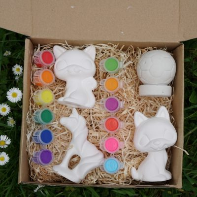 cardboard box containing four clay figurines and 2 sets of paints